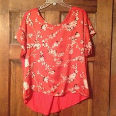 Red high-low top Front is red silky material with Black and Tan flower designs. Back is plain red stretchy material. 100% polyester material. No holes or frays or runs. Charming Charlie Tops
