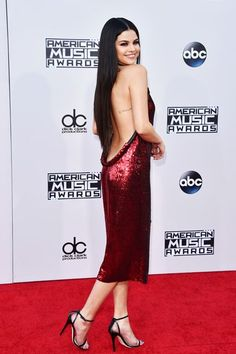 Selena Gomez AMA Red Carpet Outfit | Selena Gomez wears a sparkling red Givenchy dress in a new shape we've been seeing everywhere. We call it the pencil-fit midi dress. #refinery29 http://www.refinery29.com/2015/11/98166/selena-gomez-midi-dress-american-music-awards-2015
