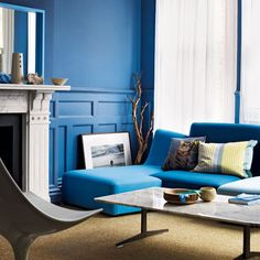Modern blue living room with dramatic blue wall color and matching sofa!
