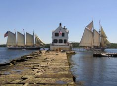 Two schooners sailing peacefully past the Rockland Breakwater Light in Maine.