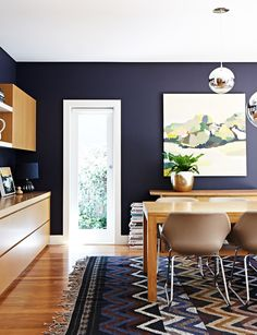 gorgeous dining room with indigo walls and wood tones