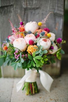 A bouquet of purple wax flowers, peach English garden roses and yellow coxcomb are the ultimate combination for a quiet backyard wedding.
