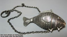 This Silver Fish Judaica spice container is marked 830 Silver N.M. 1118, which is the mark of Nicolai Soren Munch of Copenhagen Denmark. The ring is marked with English sterling marks. Inside has gold wash. The head opens to fill with the spice and the mouth opens for pouring the spice. Has a flexible body that is engraved with intricate designs.
