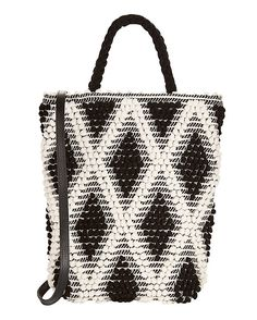 Antonello Tedde Ardara Bucket Bag: Hand made in Italy using traditional looms of cotton. Two top handles and leather shoulder strap. Magnetic closure at top. Interior drop down pockets. Measures: 14 H x 12.5 L. Lined. In black/white. Fabric: 100% cotton Lining: 100% cotton   Made in ...