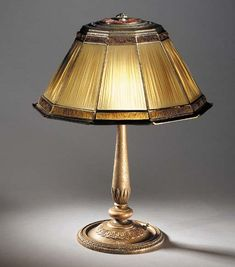 A 'FAVRILE FABRIQUE' LEADED GLASS AND GILT-BRONZE TABLE LAMP   Tiffany Studios, circa 1915   21¼in. (54cm.) high, 16½in. (41.9cm.) diameter of the shade, with a 'favrile fabrique' finial  the shade stamped 10009, the 'library' base stamped TIFFANY STUDIOS NEW YORK A3624 ½