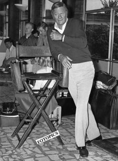 John Wayne at  Heathrow airport, England in August 1974 / The leather chair was given to him by Pappy Ford and Duke used it on location for all his movies. Wayne was in England to shoot  BRANNIGAN 1975