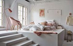 Un lit mis en scène sur une estrade très haute, qui permet de créer des rangements en dessous.