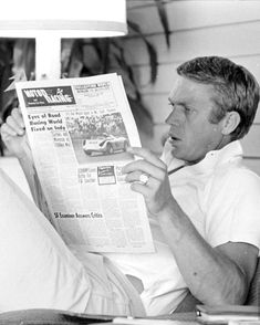 Steve McQueen reading the Motor Racing paper at home, photographed by John Dominis, 1963.