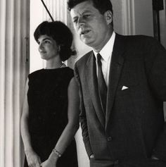 President Kennedy with his loving wife while inside the white house. Jackie is leaning against a pillar while jack is standing next to her.