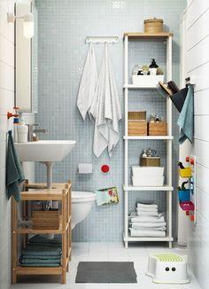 Kis családi fürdőszoba, fehér és világoskék csempével, magas fehér nyitott polcos elemmel.