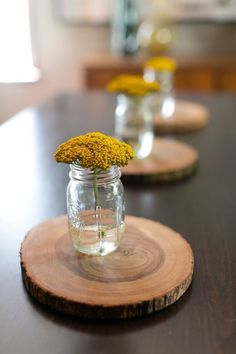 wood slices with flowers in mason jars! Makes a simple and sophisticated center piece