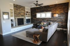 Endearing Living Room Set with Dark Wooden Flooring and L Shaped Fabric Grey Sofa Living Room Idea and Rectangular Shaped Carpet Area and Ceiling Fans Set and Stacked Stone Fire Place and Lamp