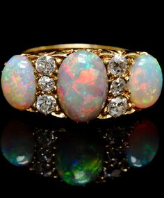 An Antique 18 Karat Yellow Gold, Opal and Diamond Ring, containing one oval cabochon crystal opal weighing approximately 2.00 carats, two oval cabochon cut crystal opals weighing approximately 1.50 carats total and six old mine cut diamonds weighing approximately 0.46 carat total.