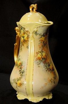 A gorgeous Limoges chocolate pot decorated with four panels of trailing yellow roses on a beautiful soft yellow, pink and blue mottled ground accented by raised gold highlights. A gilded handle and fi