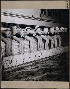 """Eight female swimmers, members of the Ottawa """"Aquamaids,"""" a Canadian Welfare Club, ready to dive into a pool at an Ottawa YMCA, March 1946."""