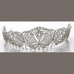 A diamond and platinum tiara designed with graduating foil motifs with garland and fan accents, set throughout with old mine, old European, old single and rose-cut diamonds; larger old European-cut diamonds weighing an estimated 1.15 and 1.05 carats; estimated total diamond weight: 19.00 carats.