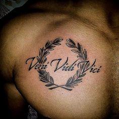 Veni Vidi Vici tattoo in an olive wreath on the chest