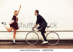 Young vintage hipster pretty couple having fun outdoor in summer on the street in city with cool bicycle behind white wall. Man with girl in spring urban style - stock photo