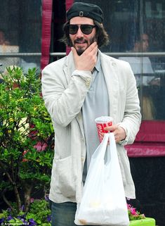 Happy: Keanu Reeves was spotted looking smiling and relaxed as he strolled around the coastal town of Punta del Esta in Uruguay on Monday ah...