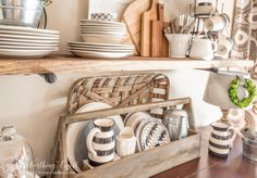 A vintage looking wood toolbox filled with white, gray and black plates looks right at home on the sideboard of a farmhouse style breakfast area and rustic shelf vignette.