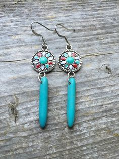 These fun earrings hang 2 1/2 long. The decorative and colorful disc as the focal is 1/2 in width, paired with a magnesite spike A nice pop of color for any outfit!  Silver plated brass ear wires. Very cute and on the lighter to medium side in weight