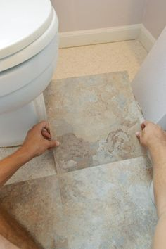 Installing stick-down laminate tiles in a bathroom - easy to stick, easy to cut, and this link includes a little tip for how to custom-cut curved edges (like around toilets, sinks, etc.)