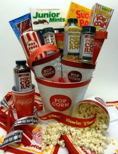 Movie Night: This one is really poppin'! Our deluxe movie night popcorn gift basket starts with our reusable popcorn buckets. They feature a removable insert to catch unpopped kernels and we've included enough for the whole family to share!  Our delicious premium popcorns and gourmet seasonings are paired with a ceramic seasoning shaker. Perfectly themed linen snack napkins and lots of classic candy favorites make this movie night collection complete. It's certainly a unique gift basket they...