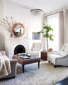 fireplace, arrangement, curtains, chairs, ottoman (via Elle Decor)