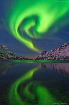 The northern lights or aurora borealis swirls over a fjord in the Norwegian Sea near Tromso, northern Norway. I would love to see this awesome spectacular mother nature displays for us all to enjoy Aurora Borealis From Space, See The Northern Lights, Fjord, Voyage Europe, All Nature, Beautiful Sky, Beautiful Places, Belle Photo, Places To See