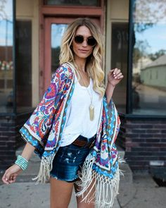 We love the fringe on this layering piece! The stunning Gypsy Travels Kimono has rich shades of coral, cream and blue! This beauty has a luxe feel and knit fabrication! Simply chic with long taupe fri