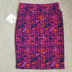 """Lularoe Cassie Skirt - Medium Beautiful geometric/mosaic design! Shades of pink and purple (also a few scattered orange) on a navy blue background. Cassie skirt features a yoga band top which can be folded over if desired, and fabric provides lots of stretch! Re-posh, 1 previous owner before me. NWT/EUC, only tried on, just too big for both of us. ):  Measurements (laid flat): Across yoga band top: approx 15.5"""" Across fullest part of skirt: 18"""" LuLaRoe Skirts Pencil"""