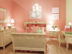 This classic pink girl's bedroom is decorated with a traditional design fit for a princess, featuring antique furniture and a vintage chandelier. Several throw pillows adorn the British cane sleigh bed, adding a plush feel to the space.