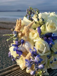 Beautiful beach inspired bridal bouquet with whites roses, blue delphinium adorned with starfish and seashells. Design by Nina at By Request.  www.byrequest.us