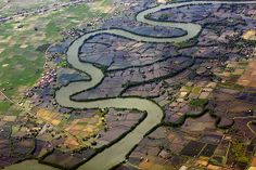 Mixed farming area of rice fields n shrimp farms transected by snaking meandering river, Makassar, Sulawesi_ Indonesia