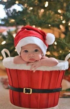 dc432a6d7e60a Baby with Santa Claus Hat sitting In Santa Basket Baby Christmas Pictures
