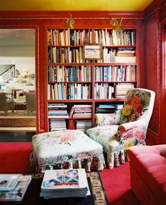 Bookshelf Photo - A floral chair and ottoman in a sitting room with red walls and brass sconces