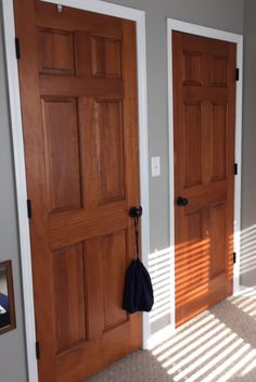 Wood stained doors, aged bronze door knobs, white trim, Woodlawn colonial paint from Valspar
