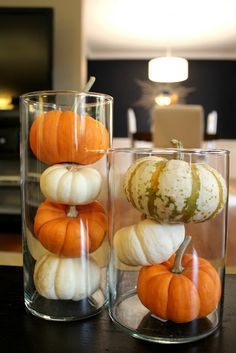Stack mini pumpkins into tall hurricane glasses to create a fall centerpiece