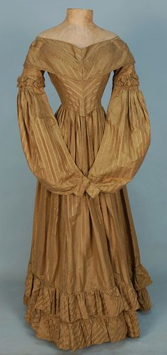 SILK GOWN with WOVEN STRIPE, c. 1836. Olive-gold satin having semi-boned princess bodice with padding, pleated self overlay at bust creating extra fullness, trimmed with twisted self piping, long sleeve ballooning below ruched band into narrow cuff, double hem ruffle, bodice lined in polished linen. - whitakerauction