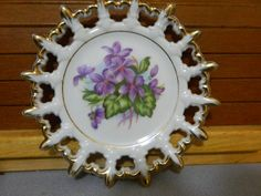 A Little Decorative Plate Hand Painted With Purple Flowers
