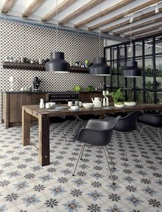 Different design of tiles on the walls and floor, dark hardwood units and table marry up with black pendant lights and chairs.
