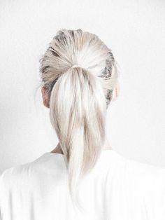 Las raíces están de su color natural y el resto del pelo cae como una cortina blanca agarrada por una colita.