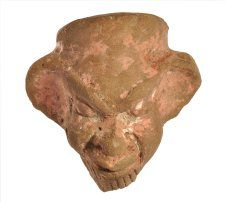 Egyptian terracotta figure. Man's bearded head with thick lips, squat nose, protruding eyes and ears.   Excavated/Findspot Naukratis  5thC BC(early)  Registration number: 1886,0401.1414