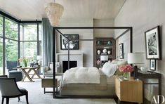 Photographs by Steven Klein and Sante D'Orazio hang in the master bedroom, on walls sheathed in a Larsen fabric. The ceiling fixture is by Ironies, the bed is by B&B Italia, and the bookcase and the table near the window are both Christian Liaigre designs. The curtains are made of a Larsen fabric, and the carpet is from Patterson, Flynn & Martin.