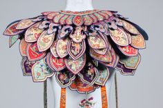 China, embroidered ceremonial collar, circa 1900, formed from multi-layered polychrome petal and cloud shaped satin panels, adorned with streamers and fringing