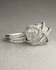 A rough diamond ring hugged by cut diamonds
