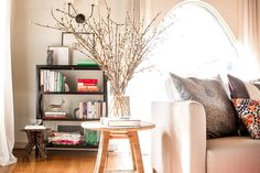 Branches as décor in living room with black bookshelf