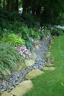 How to Handle Garden Run-Off by Creating a Dry Stream Bed - large stones and river rocks placed at the bottom of a sloped garden. This is a useful and decorative way to edge a yard - via Serenity in the Garden