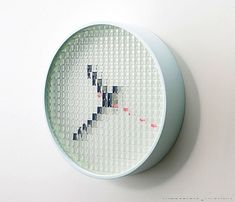 'pixel clock' designed by francois azambourg for draft. the clock's face is in honeycomb-effect fibreglass with 300 LED's, encircled by a satin white lacquered steel bezel