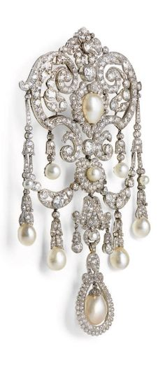 A BELLE EPOQUE NATURAL PEARL AND DIAMOND STOMACHER BROOCH, 1910S. Of openwork foliate design, set throughout with old-cut diamonds, with natural pearl fringe accents, 14.5 cm.